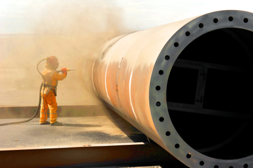 Industrial sandblasting on a large pipe